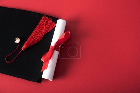 Photo for Top view of diploma with beautiful bow and graduation cap with tassel on red background - Royalty Free Image