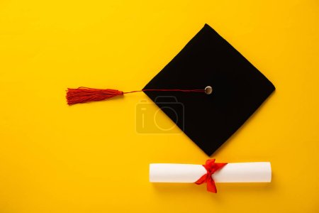 Photo pour Vue du dessus du diplôme avec bel arc et casquette de graduation avec pompon rouge sur fond jaune - image libre de droit