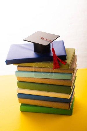 Photo pour Couvercle de graduation avec panache rouge sur fond jaune sur fond blanc - image libre de droit
