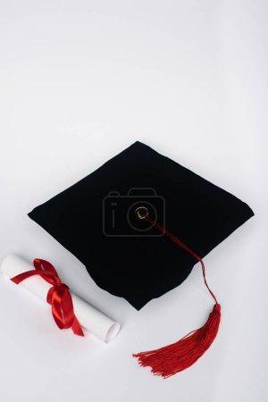 Photo pour Casquette noire avec panache rouge et diplôme sur fond blanc - image libre de droit