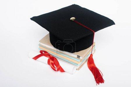 Photo pour Casquette noire avec panache rouge sur le dessus des livres et diplôme avec arc isolé sur blanc - image libre de droit