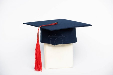 Photo for Graduation cap with red tassel on book on white background - Royalty Free Image
