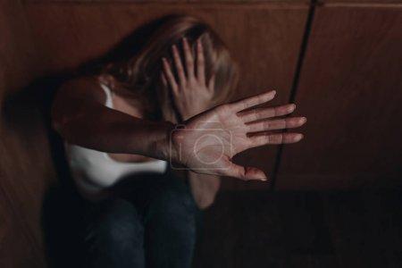 Foto de Enfoque selectivo de la mujer con cara oscura mostrando parada y escondido en la esquina - Imagen libre de derechos