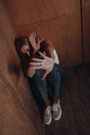 Foto de Enfoque selectivo de la mujer con cara oscura mostrando parada y sentado en la esquina - Imagen libre de derechos