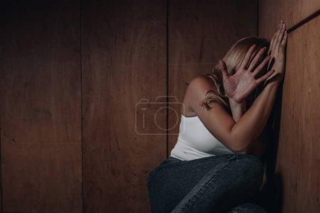 Foto de Víctima con cara oscura mostrando parada y sentada en esquina - Imagen libre de derechos