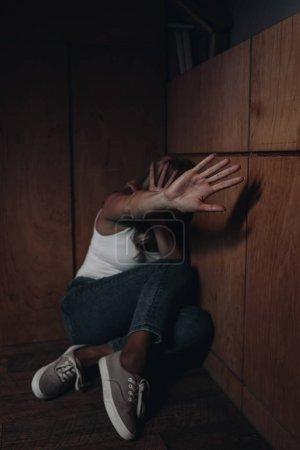 Foto de Enfoque selectivo de la mujer con cara oscura mostrando parada mientras se esconde en la esquina - Imagen libre de derechos