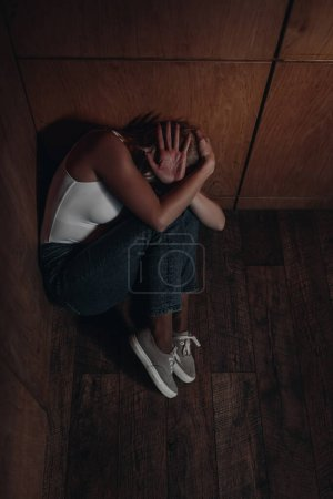 Foto de Víctima asustada cubriendo la cabeza, escondida en la esquina - Imagen libre de derechos