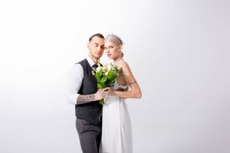 beautiful tattooed bride with bouquet and handsome bridegroom on white
