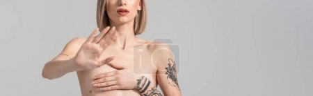 Photo pour Cropped view of sexy young topless tattooed woman showing no gesture isolated on grey, panoramic shot - image libre de droit
