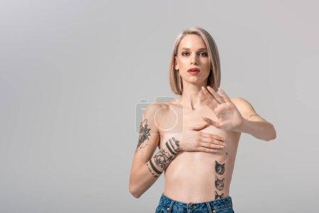 Foto de Sexy young topless tattooed woman showing no gesture isolated on grey - Imagen libre de derechos