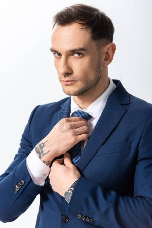 Photo for Successful tattooed young businessman in blue suit adjusting tie isolated on white - Royalty Free Image