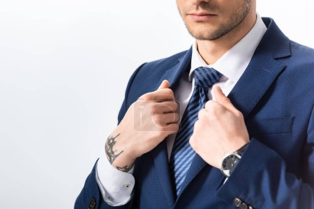 Photo pour Vue recadrée de succès tatoué homme d'affaires en costume bleu avec les mains sur blazer isolé sur blanc - image libre de droit