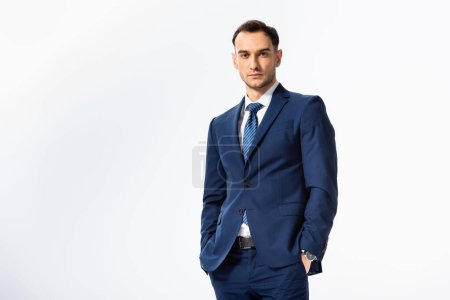 Photo for Successful young businessman in blue suit with hands in pockets isolated on white - Royalty Free Image