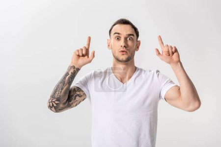 shocked handsome young tattooed man pointing with fingers up isolated on white