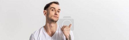 Photo pour Beau jeune homme tatoué pointant du doigt isolé sur blanc, panoramique - image libre de droit