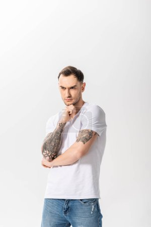 Photo for Serious handsome young tattooed man looking away isolated on white - Royalty Free Image
