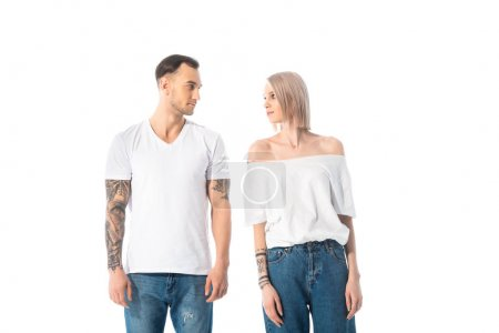 young tattooed couple looking at each other isolated on white