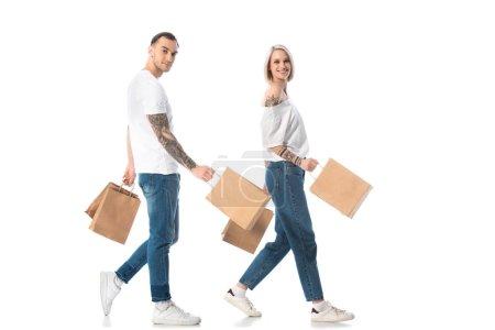 Photo pour Jeune couple tatoué marchant avec des sacs à provisions isolés sur blanc - image libre de droit