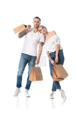 Photo pour Jeune couple tatoué avec des sacs à provisions sur blanc - image libre de droit
