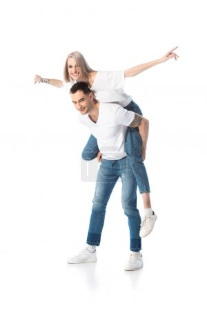 Photo for Happy young tattooed couple piggybacking isolated on white - Royalty Free Image