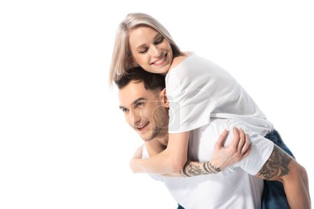 Photo for Happy young tattooed couple piggybacking isolated on white - Royalty Free Image