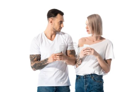 Photo for Young tattooed couple using smartphones and looking at each other isolated on white - Royalty Free Image
