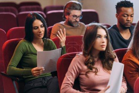 Photo pour Acteurs et actrices multiethniques lisant des scénarios sur des sièges dans le théâtre - image libre de droit