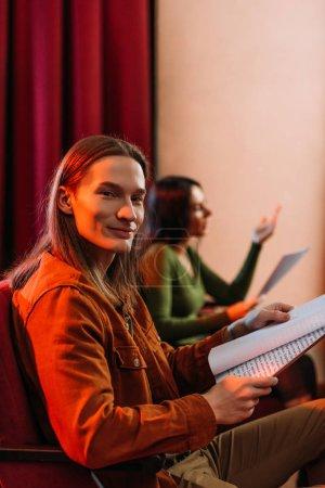 Photo pour Accent sélectif des jeunes acteurs et actrices lisant des scénarios dans le théâtre - image libre de droit
