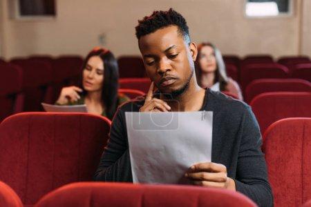 Photo pour Jeune acteur et actrices lisant des scénarios dans le théâtre - image libre de droit