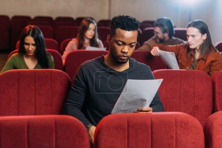 Photo pour Acteur afro-américain lecture scénario sur les sièges dans le théâtre - image libre de droit