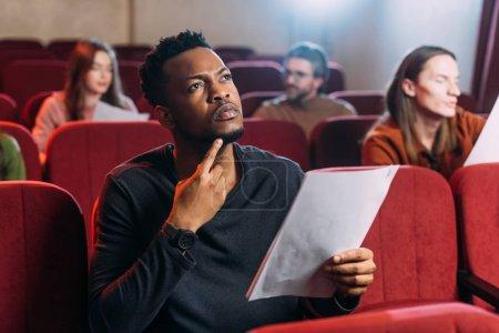 Photo pour Jeunes acteurs multiethniques lisant des scénarios dans le théâtre - image libre de droit
