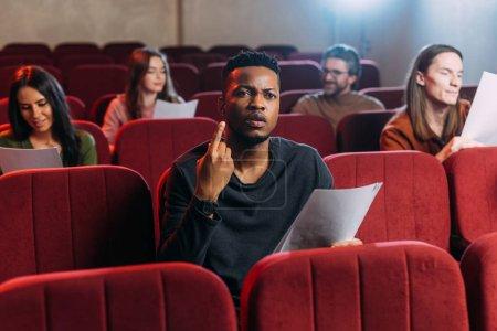 Photo pour Acteur afro-américain répétant et pointant vers le haut tout en étant assis sur des chaises rouges avec des acteurs - image libre de droit