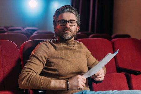 Photo pour Metteur en scène barbu avec scénario sur les sièges dans le théâtre - image libre de droit