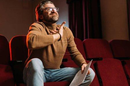 Photo pour Metteur en scène émotionnel avec scénario sur les sièges dans le théâtre - image libre de droit