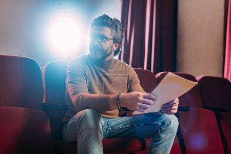 Photo pour Metteur en scène mature avec scénario dans le théâtre avec rétroéclairage - image libre de droit