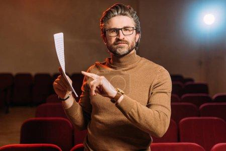 director de escena madura emocional apuntando al escenario en el teatro