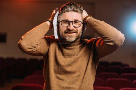 Photo pour Beau metteur en scène émotionnel avec scénario sur la répétition au théâtre - image libre de droit