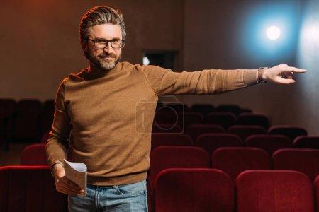 Photo pour Metteur en scène émotionnel avec scénario pointant sur la répétition dans le théâtre - image libre de droit
