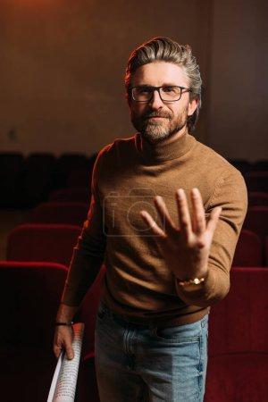 Photo pour Metteur en scène émotionnel avec scénario gestuelle sur la répétition au théâtre - image libre de droit