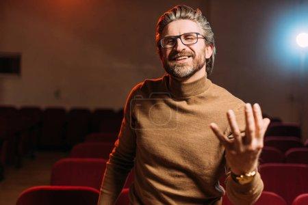 Photo pour Metteur en scène positif avec scénario de répétition au théâtre - image libre de droit