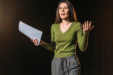 hermosa actriz emocional realizar papel con guion en negro
