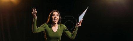 Photo pour Plan panoramique d'actrice émotionnelle attrayante jouant le rôle sur noir - image libre de droit