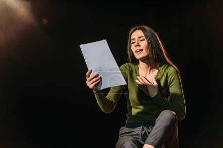 Photo pour Attrayant scénario de lecture actrice émotionnelle sur noir - image libre de droit
