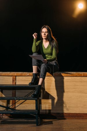 beautiful young actress reading scenario on stage in theatre