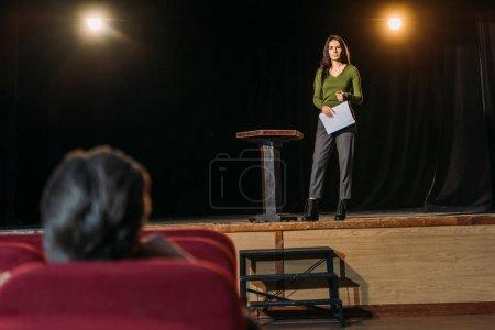 Photo pour Mise au point sélective du metteur en scène et belle actrice avec scénario sur scène - image libre de droit