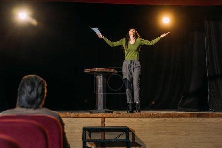 Photo pour Focalisation sélective du metteur en scène et de l'actrice jouant un rôle sur scène - image libre de droit