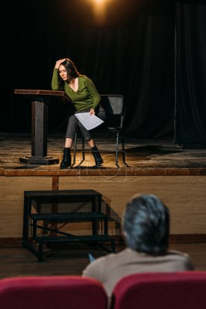 Photo pour Mise au point sélective du metteur en scène de théâtre et belle actrice jouant le rôle sur scène - image libre de droit