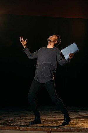 Photo pour Acteur afro-américain tenant scénario sur scène pendant la répétition - image libre de droit