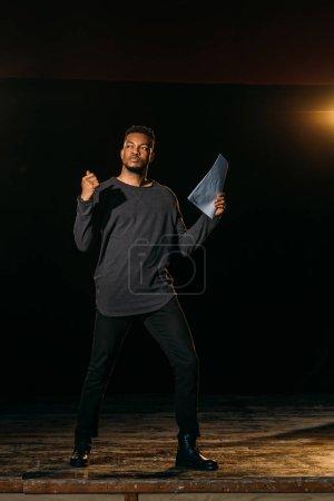 Photo pour Acteur afro-américain tenant le scénario et debout sur scène pendant la répétition dans le théâtre - image libre de droit