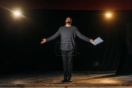 Photo pour Acteur afro-américain tenant scénario et debout sur scène pendant la répétition - image libre de droit